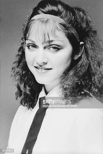 A studio headshot portrait of future American pop singer Madonna smiling while wearing a white cotton shirt with a dark tie New York City She wears a...