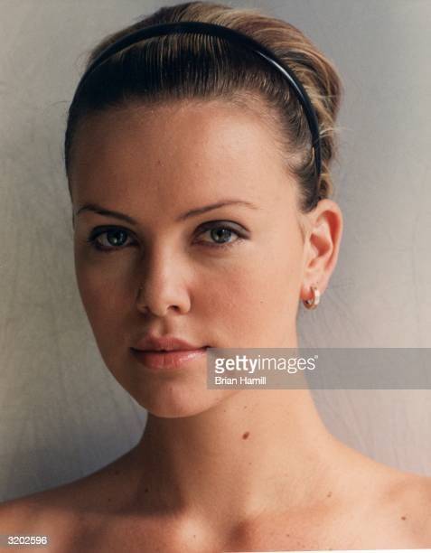Studio headshot portrait of South Africanborn actor Charlize Theron wearing a headband in her hair and a gold earring New York CityTheron is...