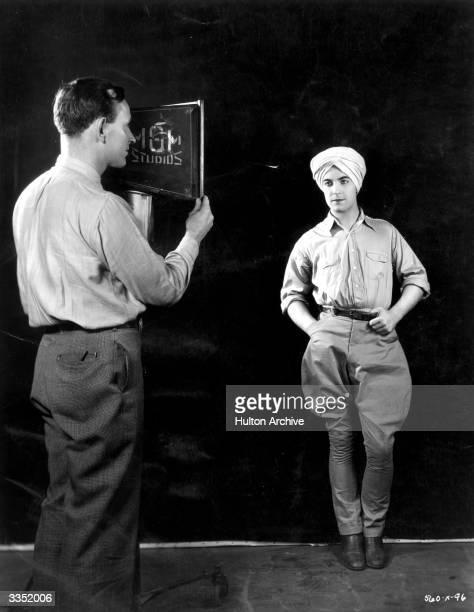 A studio lighting technician positions the spotlight on actor Ramon Novarro hearthrob star of the new MGM film 'Son of India'