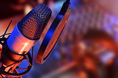 Studio microphone with headphones and mixer background with blue and red lights live production. Elevated view