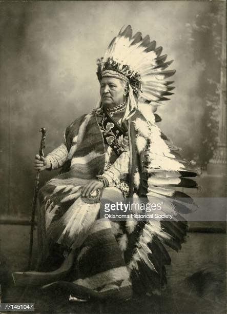 Studio photograph of Pleasant Porter Chief of the Creek Indian Nation who is wearing a Plains Indian feathered headdress Muskogee Indian Territory...