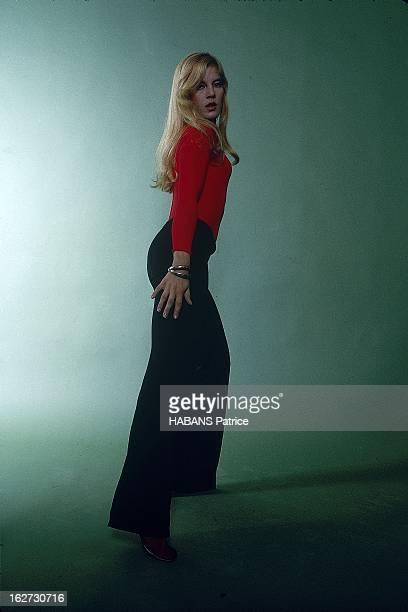 Studio Picture Of Sylvie Vartan Attitude de Sylvie VARTAN vêtue d'un pantalon noir et d'un pull rouge