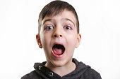 Studio portrait cute boy screaming at the camera