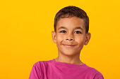 studio portrait of a 10 year old schoolboy on a yellow background