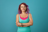 Studio portrait of a 30 year old woman with purple hair on a blue background