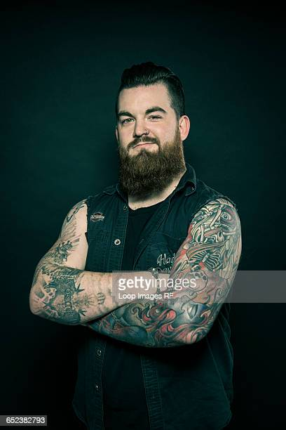 Studio portrait of a bearded man with tattooed arms