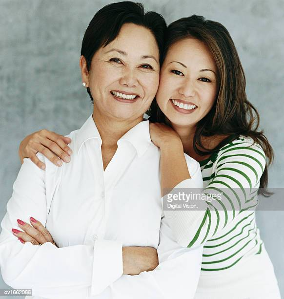 Studio Portrait of a Daughter With Her Arm Around Her Mother, Smiling at the Camera