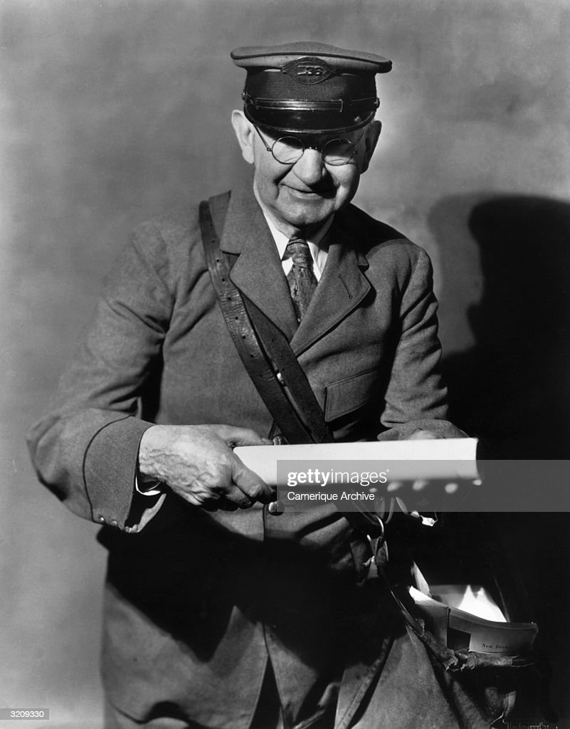 Studio portrait of a New York post official smiling while holding a piece of mail he has pulled from his bag.