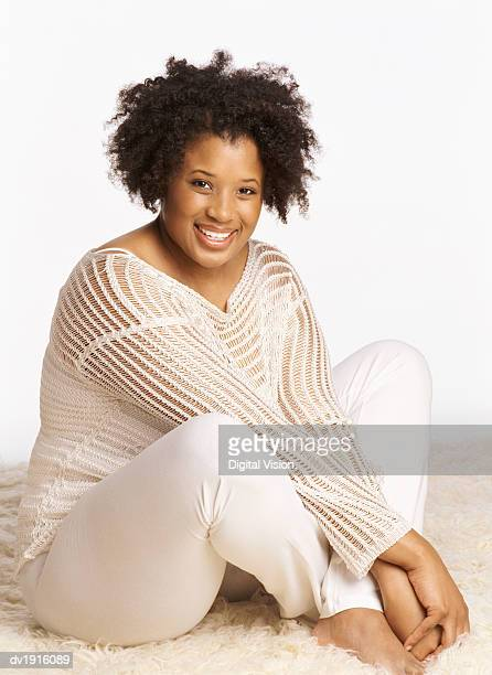 Studio Portrait of a Smiling Woman Sitting on a Rug