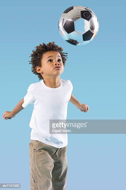 Studio Portrait of a Young Boy Heading a Silver Football