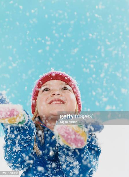 Studio Portrait of a Young Girl in Winter Clothing Looking up and Catching Snowflakes on Her Mittens
