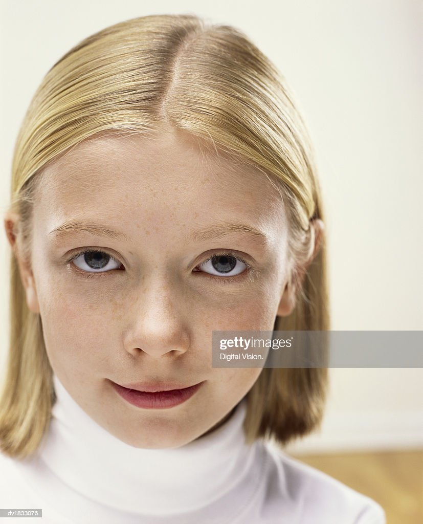 Studio Portrait of a Young Girl Wearing a White Polo-Neck Jumper : Stock Photo