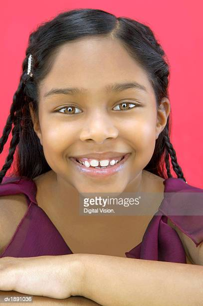 Studio Portrait of a Young Girl With Braided Hair and a Toothy Smile