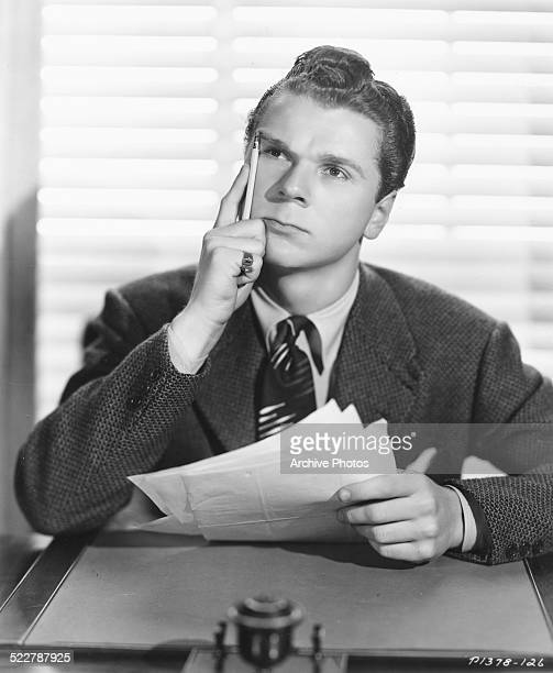 Studio portrait of actor Jackie Cooper sitting at desk deep in thought circa 1940