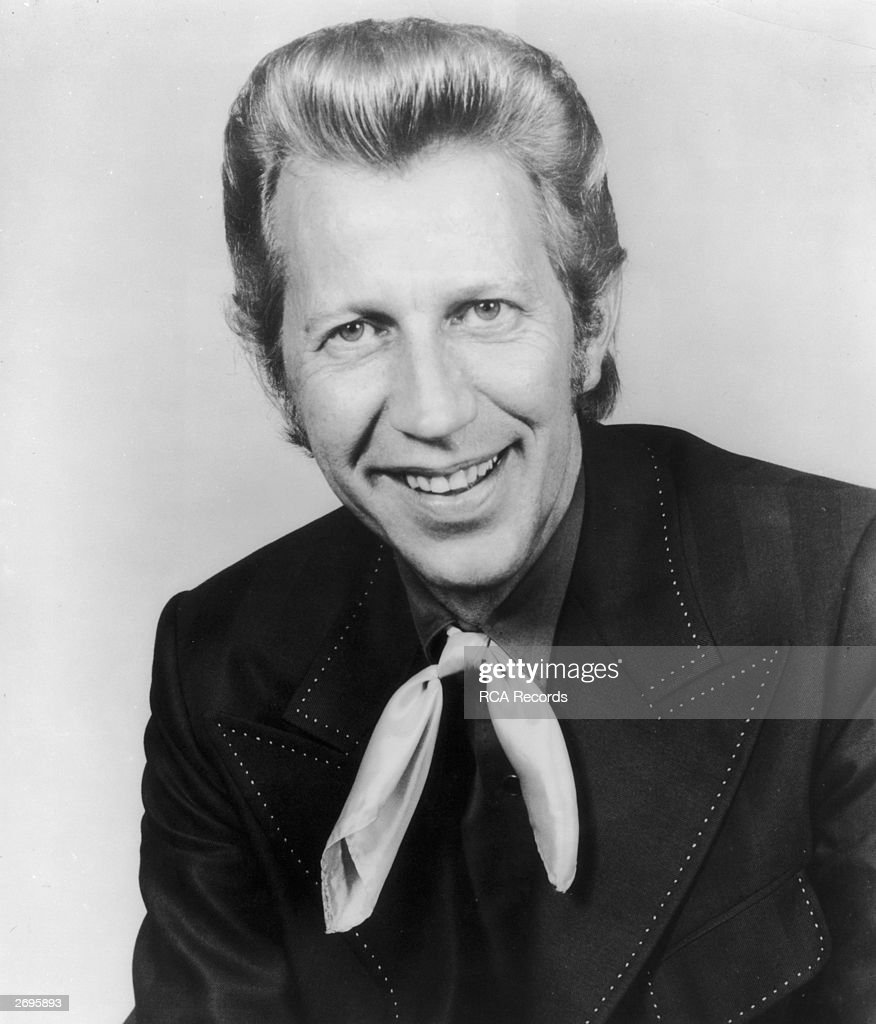Studio portrait of American country singer Porter Wagoner smiling in a ribbon tie and a jacket with wide lapels, 1970s.
