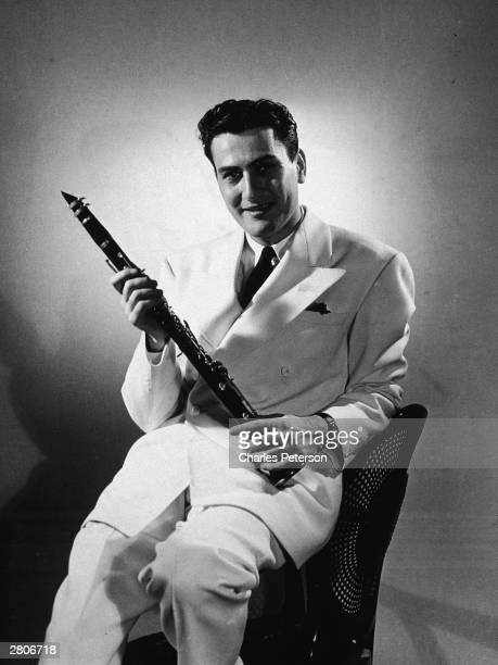 Studio portrait of American jazz musician and bandleader Artie Shaw with a clarient and dressed in a white suit circa 1935