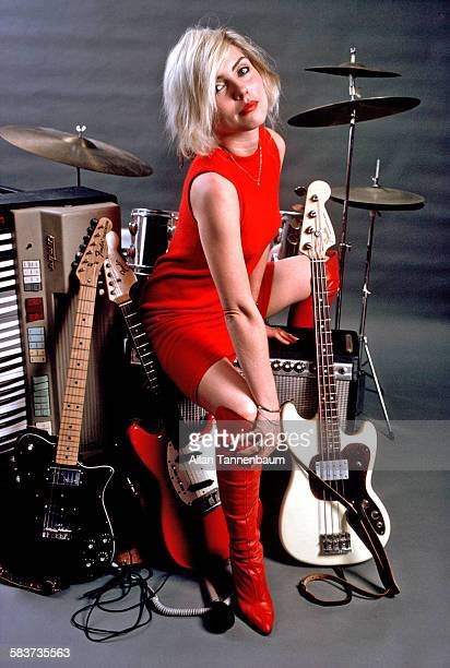 Studio portrait of American musician Debbie Harry of the group Blondie in a red dress as she poses seated atop various musical instruments New York...