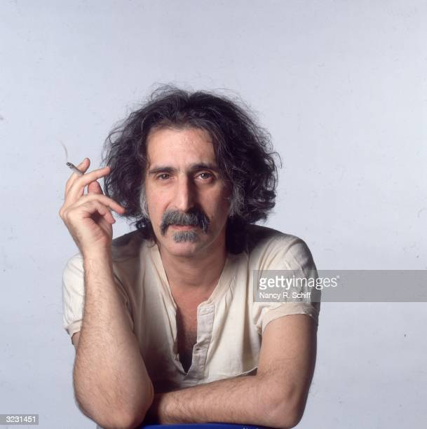 Studio portrait of American rock musician Frank Zappa smoking a cigarette