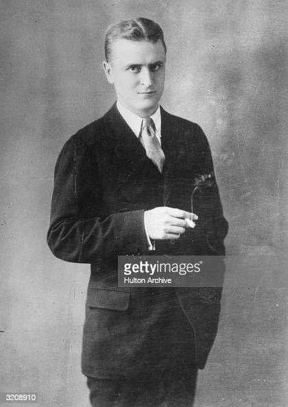 A studio portrait of American writer F Scott Fitzgerald wearing a suit and tie and holding a lighted cigarette