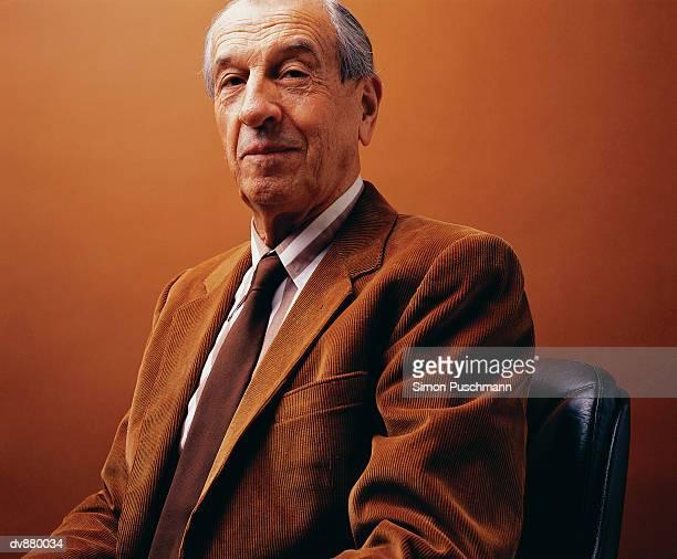 Studio Portrait of an Elderly Man Sitting in a Corduroy Jacket