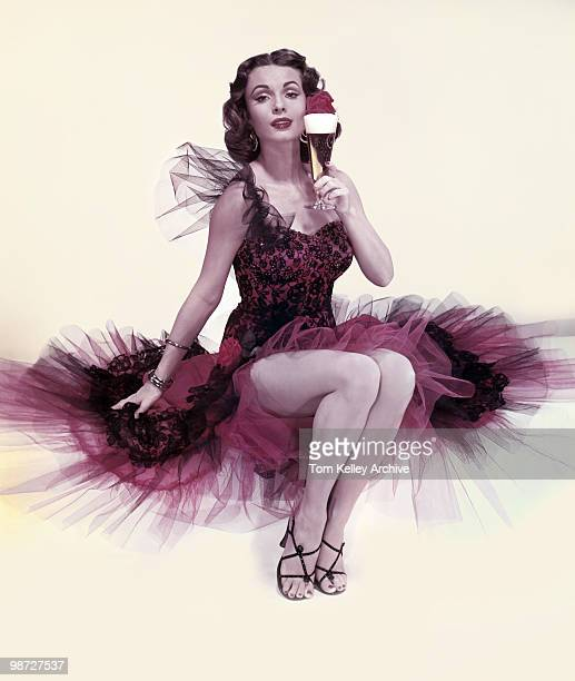 Studio portrait of an unidentified model in a red and black cocktail dress with a chiffon skirt as she poses with a glass of beer in one hand 1953
