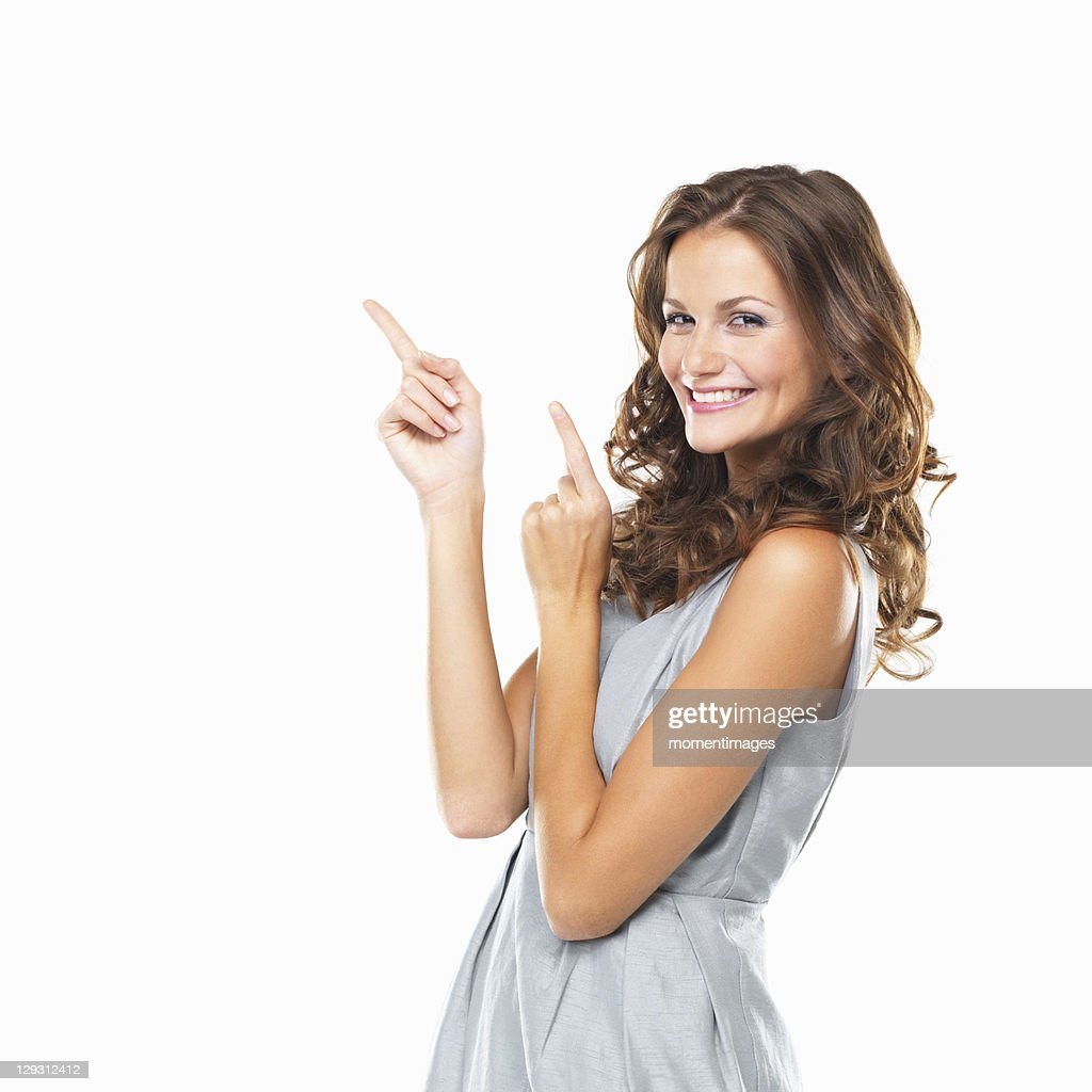 Studio portrait of beautiful smiling woman pointing upwards : Photo