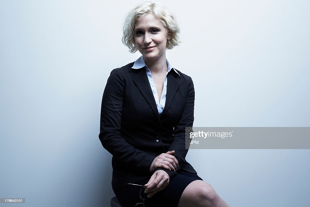 Studio portrait of blond businesswoman sitting on stool