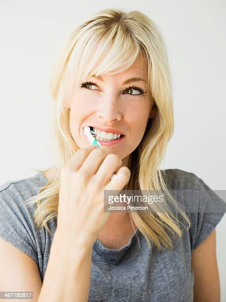 Studio portrait of blonde woman cleaning teeth