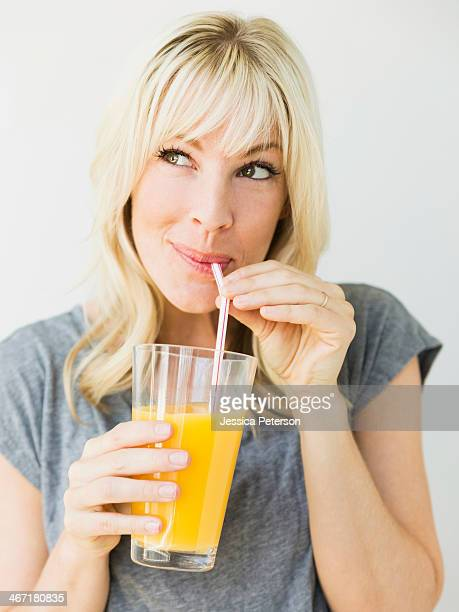 Studio portrait of blonde woman drinking orange juice