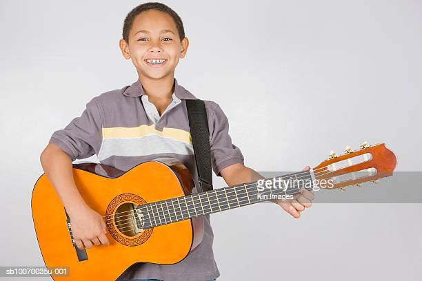 Studio portrait of boy (8-9) playing guitar