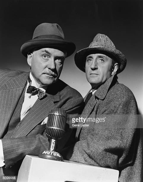 Studio portrait of British actor Nigel Bruce and South Africanborn actor Basil Rathbone posing behind a microphone Both are dressed in character...