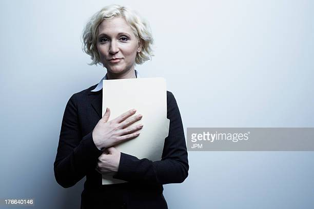 Studio portrait of businesswoman holding file