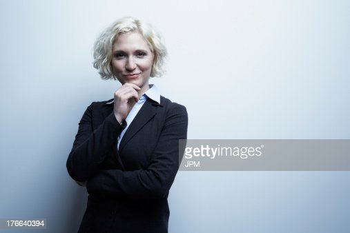 Studio portrait of businesswoman with hand on chin