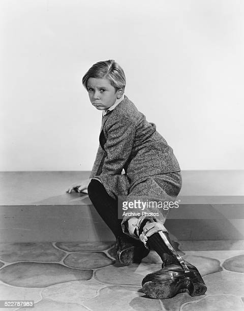 Studio portrait of child actor Jackie Cooper wearing a leg brace for MGM Studios circa 1932