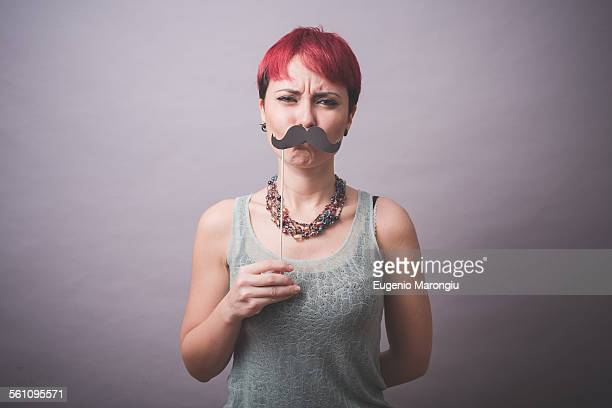 Studio portrait of confused young woman holding up mustache in front of face