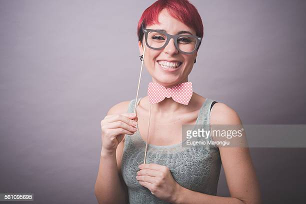 Studio portrait of confused young woman holding up spectacles in front of face