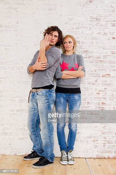 Studio portrait of couple making gun hand gestures