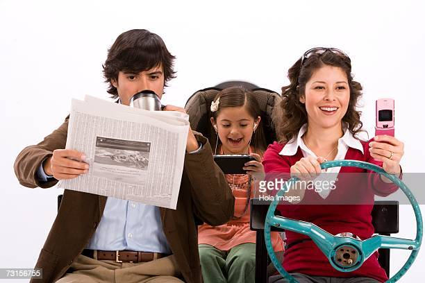 Studio portrait of distracted family in imaginary car