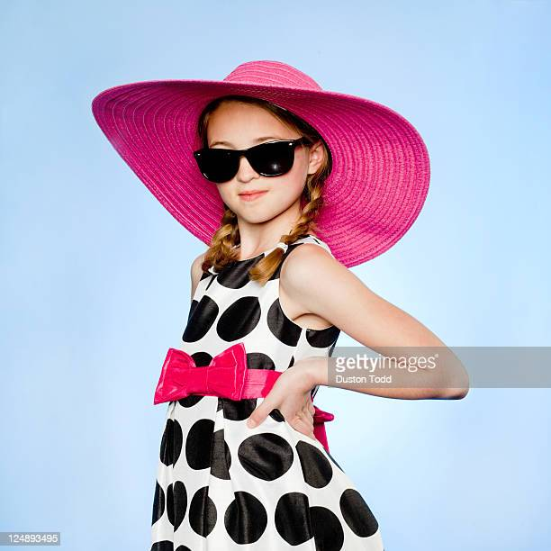 Studio portrait of elegant girl (10-11) wearing hat, sunglasses and dress