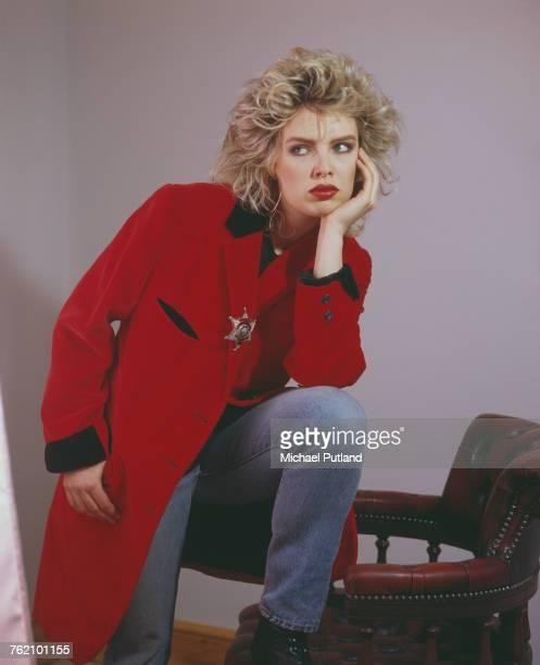 Studio portrait of English pop singer Kim Wilde posed wearing a red teddy boy style drape jacket in London in May 1985