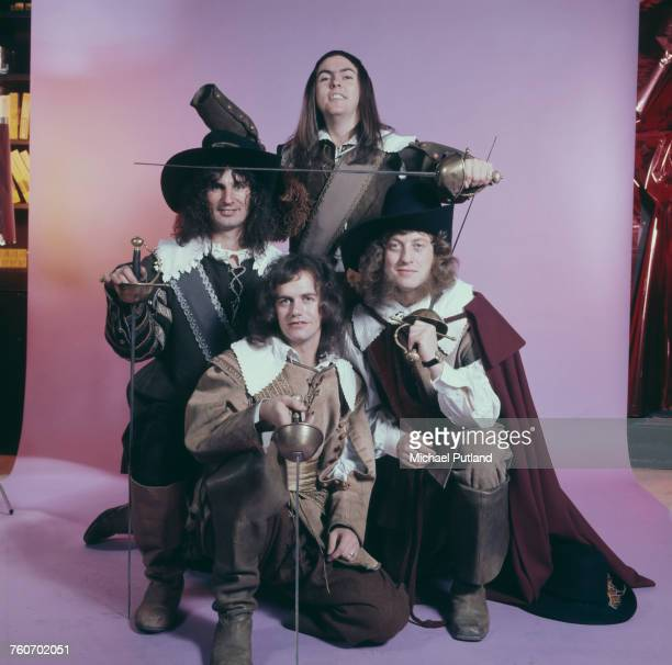 Studio portrait of English rock group Slade posing in cavalier costumes and holding swords London 1974 Clockwise from front bassist Jim Lea drummer...