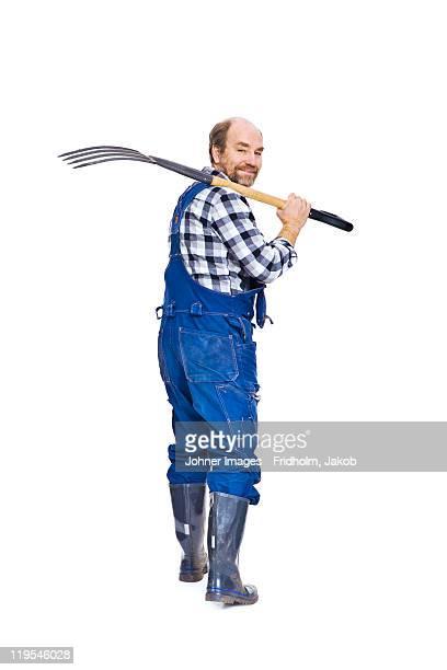 Studio portrait of farmer with pitchfork