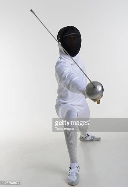 Studio portrait of fencer holding fencing foil