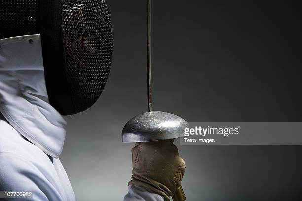 Studio portrait of fencer holding fencing foil