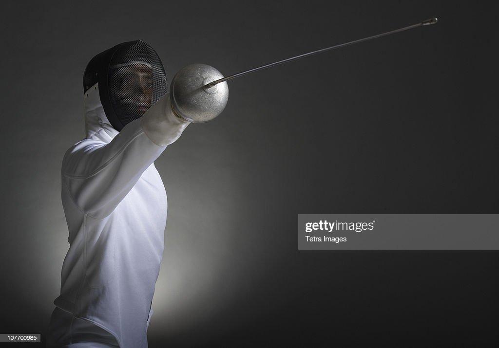 Studio portrait of fencer holding fencing foil : Stock Photo