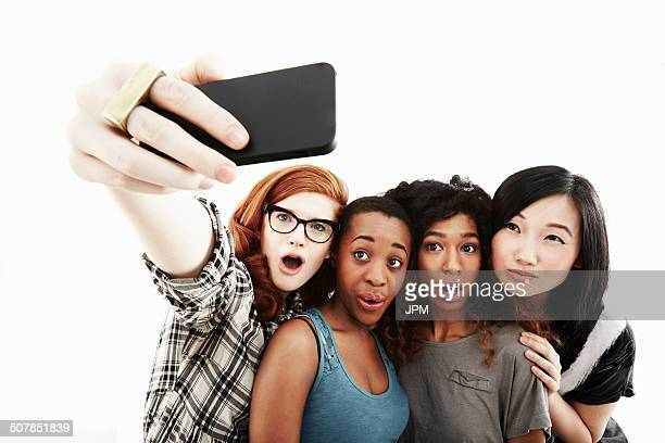 Studio portrait of four young women taking selfie on smartphone