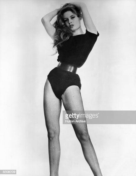 Studio portrait of French actor Brigitte Bardot wearing a black bodysuit cinched at the waist with a belt and black fishnet stockings in a...
