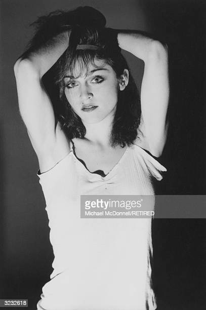 A studio portrait of future American pop singer Madonna in a cotton camisole holding her dark shoulderlength crimped hair New York City She had just...