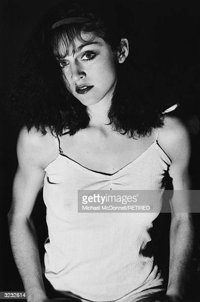 A studio portrait of future American pop singer Madonna tilting her head to one side while wearing a cotton camisole and a headband New York City Her...