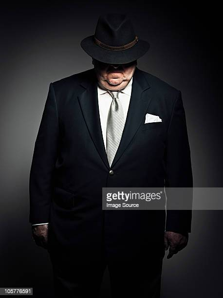 Studio portrait of gangster with hat covering face